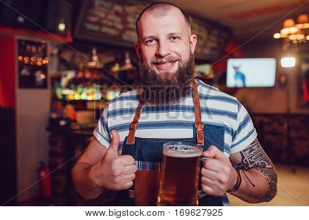 Bearded barman with tattoos wearing an apron standing in bar and holding a glass of beer