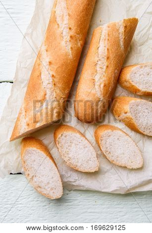 Fresh long baguette on white paper on wooden table