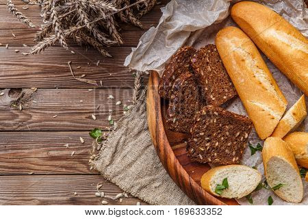 Fresh bread in wooden bowl on table with wheat and linen cloth