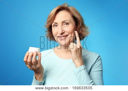 Gorgeous senior woman applying anti-aging cream on blue background