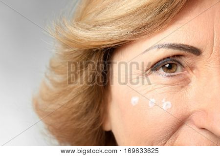 Gorgeous senior woman with anti-aging facial cream, closeup