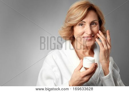 Gorgeous senior woman applying anti-aging cream on grey background