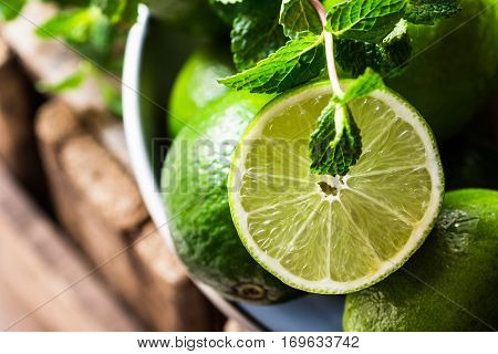 Heap of ripe organic limes cut in half in the sunlight, leaves of fresh mint, on vintage wood, ingredients for infused detox drinks, citrus, cleansing, diet,freshness, health concept