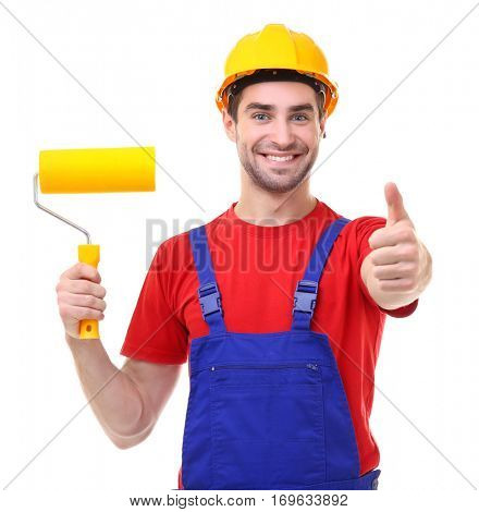 Handsome young decorator with paint roller on white background