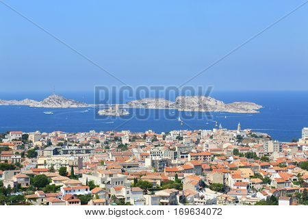 Townscape and many boats sail near IF island at sunny summer day in Marseille, France