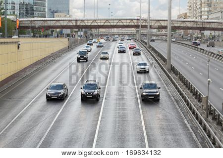Many cars ride on wet highway after cleaning in Moscow, Russia at spring day