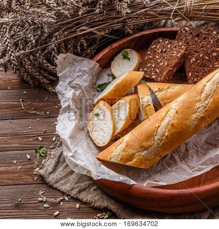 Fresh bread in wooden dish on table with wheat spikelets