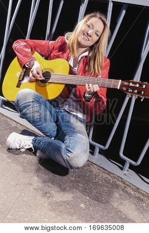 Happy Positive Caucasian Blond woman Posing in Red Leather Jacket and Jeans with Guitar Outdors on Dark Street.Vertical Composition