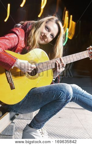 Youth Street Life Concepts. Positive Caucasian Blond Girl Playing the Guitar Outside on Street. Combination of Flash and Halogen.Vertical Image