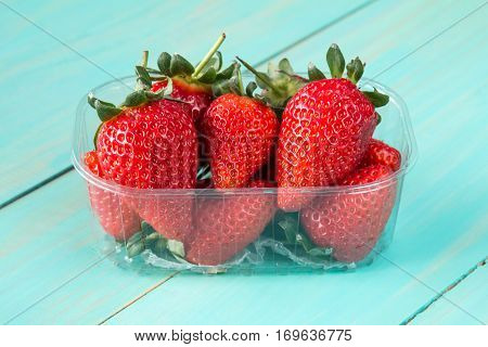 Plastic box full of red strawberries on the blue wooden background
