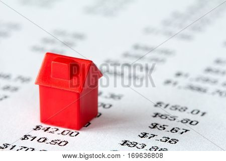 Red miniature house on a financial report background