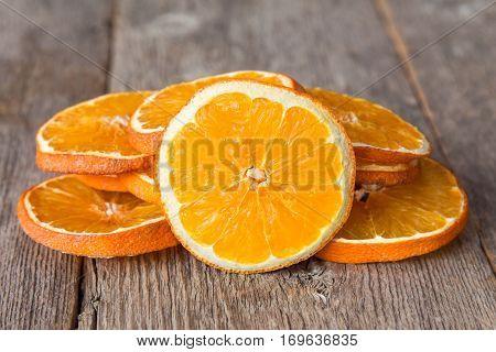 Slices of orange fruit on the wooden background