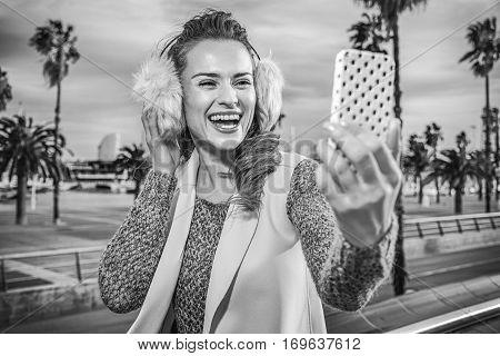 Woman On Embankment In Barcelona Taking Selfie With Smartphone