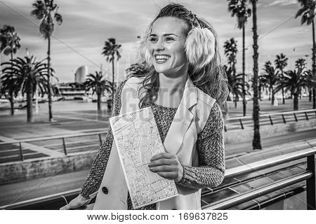 in Barcelona for a perfect winter. smiling modern tourist woman in earmuffs in Barcelona Spain having excursion