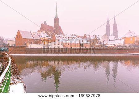 Cathedral Island or Ostrow Tumski with with Cathedral of St. John and church of the Holy Cross and St. Bartholomew in the snowy overcast winter day in Wroclaw, Poland