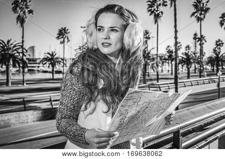 in Barcelona for a perfect winter. modern woman in earmuffs in Barcelona Spain with map looking into the distance