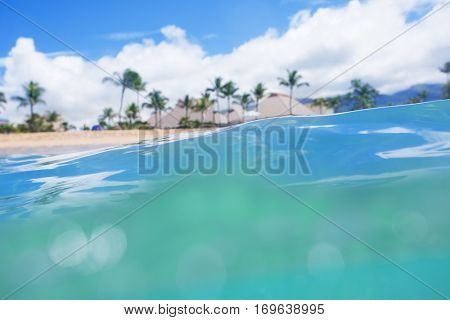 View of a Beautiful tropical island beach resort from the surface of the ocean looking back at a secluded, idyllic beach with palm trees and cabanas. focus on the surface of the water