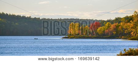 Two men in the distance floating in a small fishing boat, casting lines on a lake near the wood's edge.  Late summer colors emboldened by late afternoon, golden sunlight.