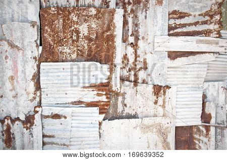 An abstract background image of rusting white corrugated iron sheets overlapping to form a wall or fence.