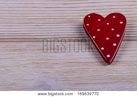 red heart on the white rustic wooden background with woodgrain texture, close up