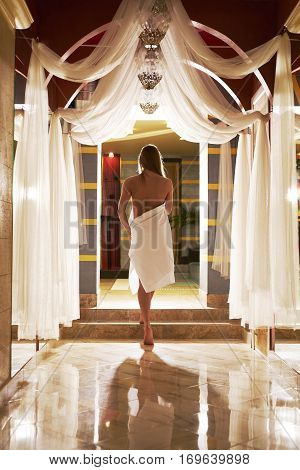 Sexy long haired blonde wrapped in white towel posing seminude with her back to viewer in luxurious sauna interior