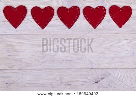 red hearts on the white rustic wooden background with woodgrain texture