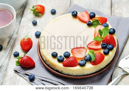 Ricotta cheesecake decorated with strawberries blueberries and mint.