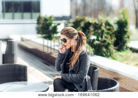 Pleasant modern attractive young woman holding mobile phone talking with friend and sitting at the table while relaxing in the cafe on buiding nature background