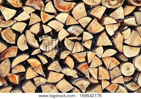 Natural wooden background. Pile of stacked triangle firewood prepared for fireplace and boiler -wooden background in natural tones. Wooden  background of firewood. Natural wooden background