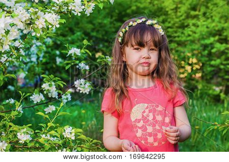 little girl with wreath from flowers on head in a blooming Apple orchard