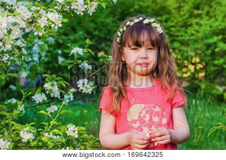 Cheerful little girl with wreath from flowers on head in a blooming Apple orchard