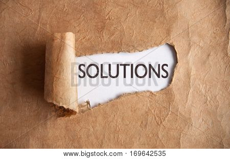 Torn piece of scroll paper uncovering solutions