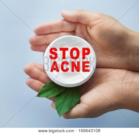 Female hands holding jar with facial cream. Text STOP ACNE on background