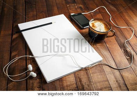 Blank paperwork template for designers. Responsive design mock up. Paper letterhead coffee cup smartphone pencil and headphones on wooden table background.