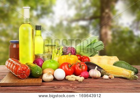 Various foodstuff on wooden table against nature background