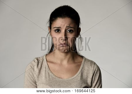 young beautiful hispanic sad woman serious and concerned looking worried and thoughtful facial expression feeling depressed isolated grey background in sadness and sorrow emotion