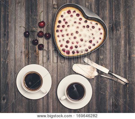 Vintage valentine day background. Homemade cherry pie heart shape silverware and two cups of coffee with fresh cherries on wooden rustic background. Selective focus.