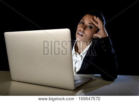young hispanic business woman or student girl working in darkness on laptop computer late at night looking bored and tired in long hours of work concept isolated on black background