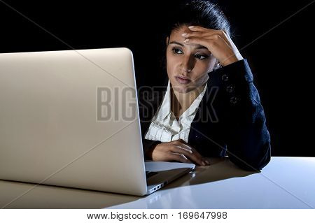 young latin business woman or student girl working in darkness on laptop computer late at night looking bored and tired in long hour of work concept isolated on black background