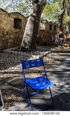 RHODES, GREECE-SEPTEMBER 23, 2016: Blue painter's chair in a shady alley. Entrance to the old town in Rhodes Town, Greece