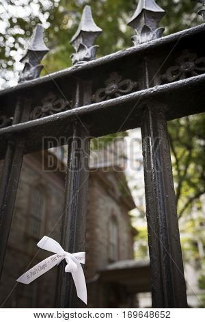 NEW YORK - SEPT 11 2016: White ribbons of remembrance tied to the iron fence of St Pauls Chapel at Ground Zero in Lower Manhattan on the 15th anniversary of the 9/11 terror attacks.