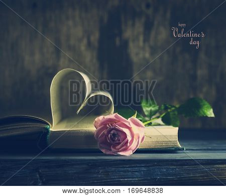Old book page with a heart-shaped Valentine's Day and a pink rose on a blue wooden table.