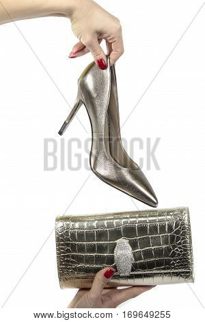 Woman holds in her hand bag and shoe isolated on a white background