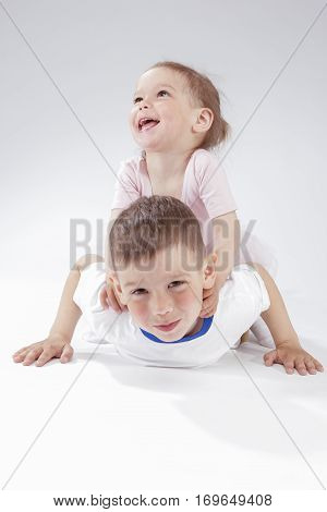 Family Ideas and Concepts. Portrait of Happy and Smiling Children Playing Together Underneath. Posing Against White. Vertical Image Composition