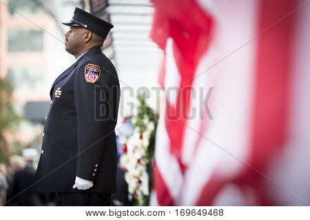 NEW YORK - SEPT 11 2016: Fire fighters take part in the ceremonial changing of the guard at the FDNY Ten House fire station lined with American Flags on the 15th anniversary of the WTC terror attacks.