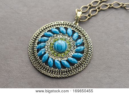 blue pendant with gems on paper background