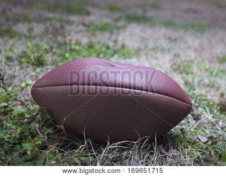 Football that is very low on air on a grassy field