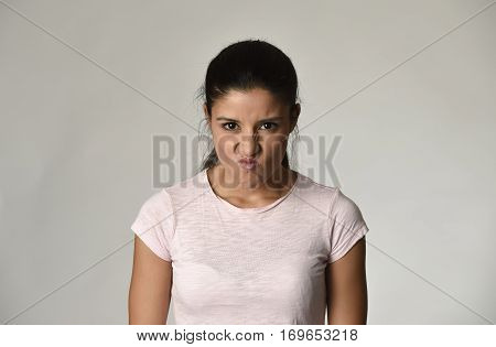 head portrait of young beautiful hispanic angry and upset woman looking furious and crazy moody in intense look and rage face expression isolated grey background in anger emotion concept