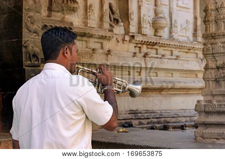 Hampi, India - November 20, 2012: Unidentified Indian man with a bugle in courtyard of the Virupaksha temple. Several times of a day bells are sounding in the temple they echo buglers and drummers