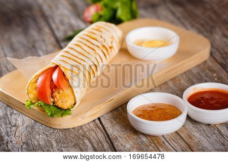 Tortilla With Chicken And Tomatoes On A Wooden Stand